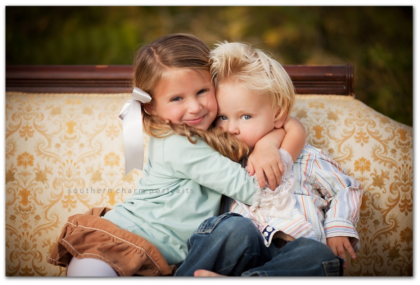 brother and sister hugging- adorable! ON VINTAGE COUCH, at that!